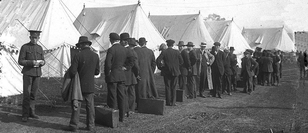 Photographie d'une file d'attente formée des hommes habillés en tenue de civil, certains ont des valises sur terre. On peut voir un soldat tenant un morceu de papier et des tentes blancs.