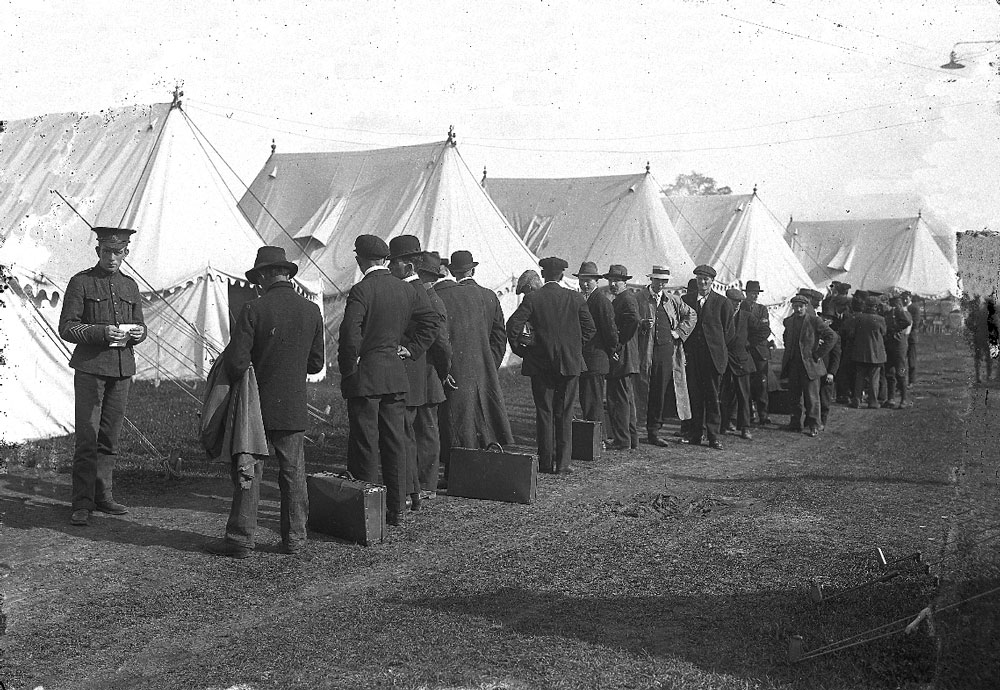 Photograph of a line up of men in civilian dress, some have suitcases on the ground. A soldier holding a piece of paper and white tents can be seen.