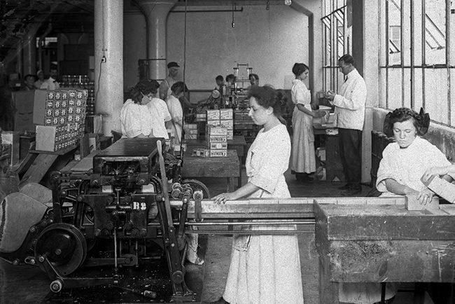 Photographie en noir et blanc dans une usine; en premier plan 2 femmes travaillent derrière une machine industrielle. Plusieurs autres personnages en arrière-plan, femmes et hommes.