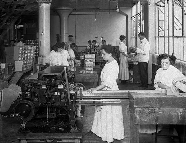 Black and white photograph in a factory; in front, 2 women are working behind an industrial machine. Other characters, women and men, in the background.