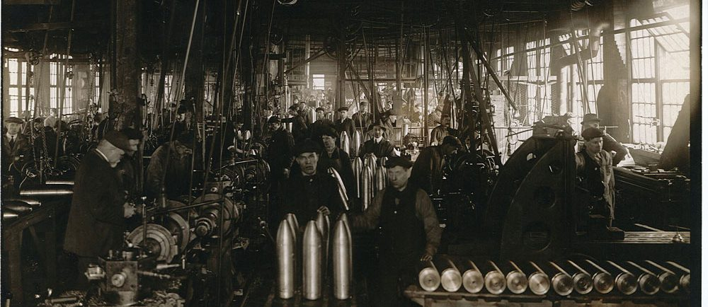 Photograph of a factory with many male workers around ammunition shells and industrial machines.