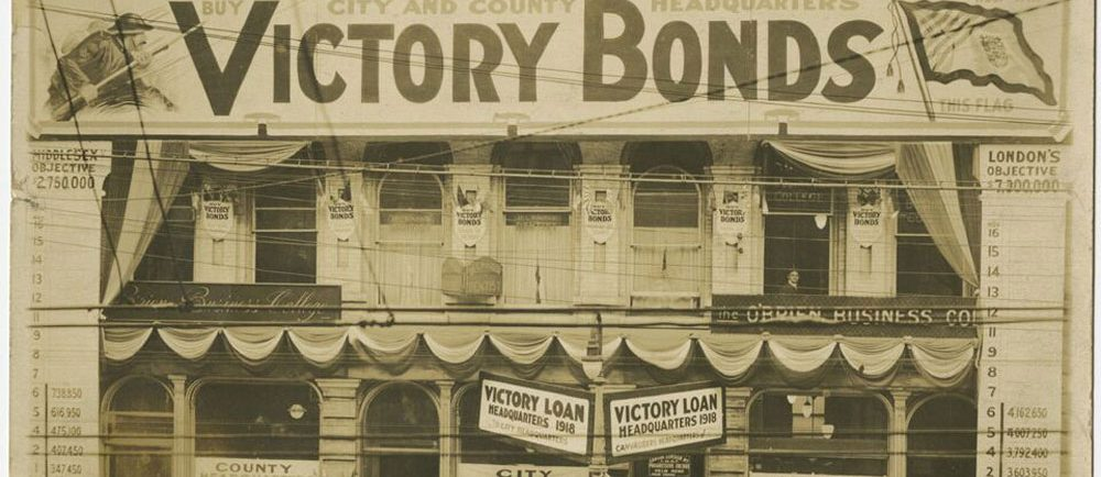 "People in front of a building with banners reading ""Victory Bonds."""