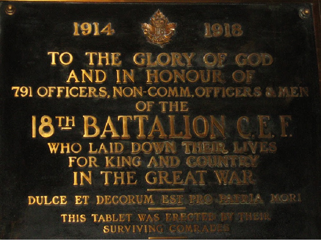 Detail of a plaque with golden lettering on dark background showing the badges of 18 Battalion CEF.