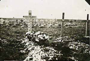 A photograph showing a graveyard with many crosses. In the foreground 3 crosses, the first is white in crowns a grave that has flowers on it.