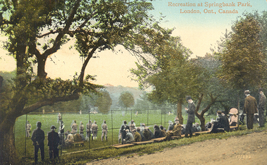 Postal card in colour, showing a group of people watching a sports game in a park.