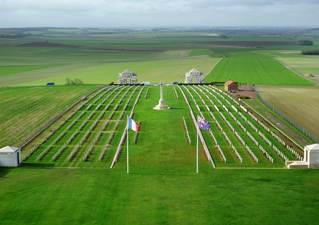 Photograph of a military cemetery ith many rows of headstones in a landscape. French and Australian flags are in front.