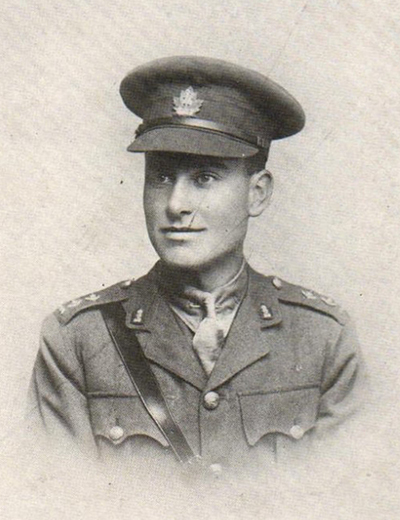 Portrait of a soldier wearing peak hat. Accoutrements and a belt can be seen on his shoulders and chest.