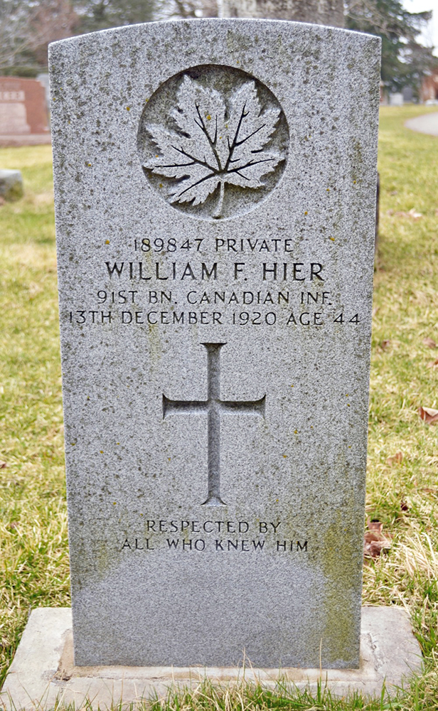 A grave stone with a cross and a maple leaf carved in.