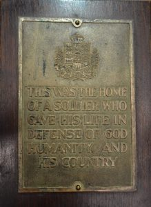"A rectangular brass plaque with coat of arms and the inscription ""This was the home of a soldier who gave his life in defense of God, humanity and his country""."