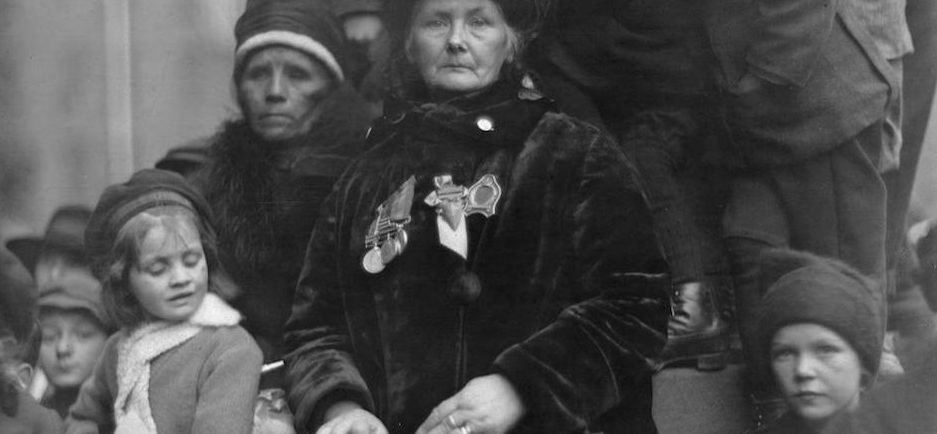 Photo représentant une femme endeuillée, arborant des médailles et tenant un sac-à-main; elle est entourée d'enfants et d'une autre femme endeuillée.