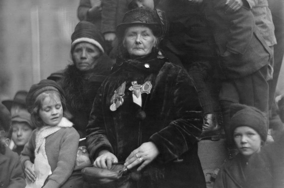 Photograph featuring a women in mourning who has medals on her chest and holds a purse; she is surrounded by children and another women in mourning.