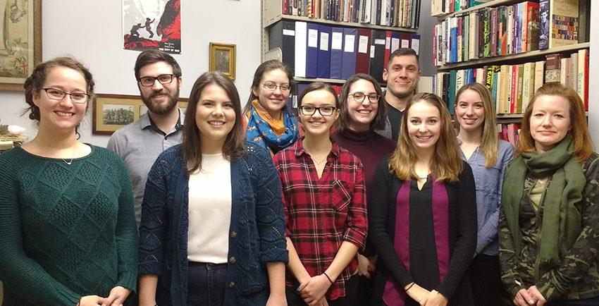 Neuf étudiants et leur enseignant devant des bibliothèques.