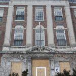 Photographie de la façade d'un bâtiment de 3 étages en brique rouge avec un set de 3 fenêtres au 2ème et au 3éme étages. Un escalier vers l'entrée s'aperçoit. Les portes d'entrée sont couvertes de placage. L'inscription « Hôpital des enfants à la mémoire de la guerre » est gravé en haut.