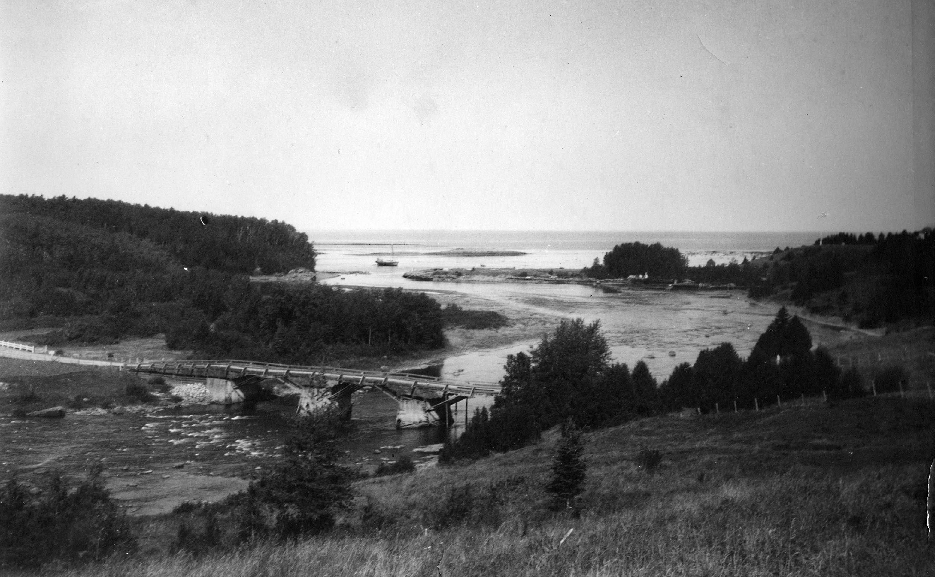 Photograph of the old wooden Bridge at Grand-Métis circa 1925. The bridge is located about 1 km from the mouth of the Metis River. Both sides of the river present a forest landscape and wharf. A schooner is moored at the mouth of the river and offers a glimpse of the expanse of the St. Lawrence River.