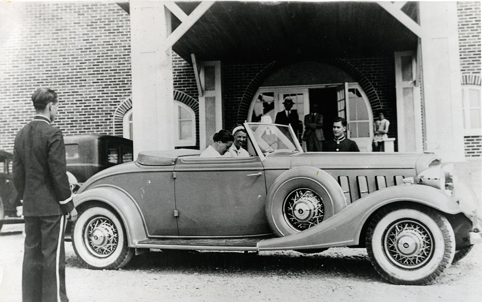 Black and white photograph. In a convertible Buick, two women, Eleanor Roosevelt and her friend Lorena Hickok, are about to depart. The car is parked at the front of the La Belle Plage hotel in Matane. A doorman and bellboy from the hotel are waiting for the departure of their distinguished guests.