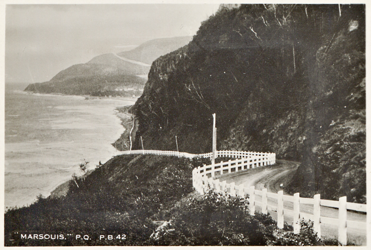 Photograph showing the winding Boulevard Perron in the municipality of Marsoui. Perron Boulevard crosses a rocky cape and is bordered by a white painted wooden fence.