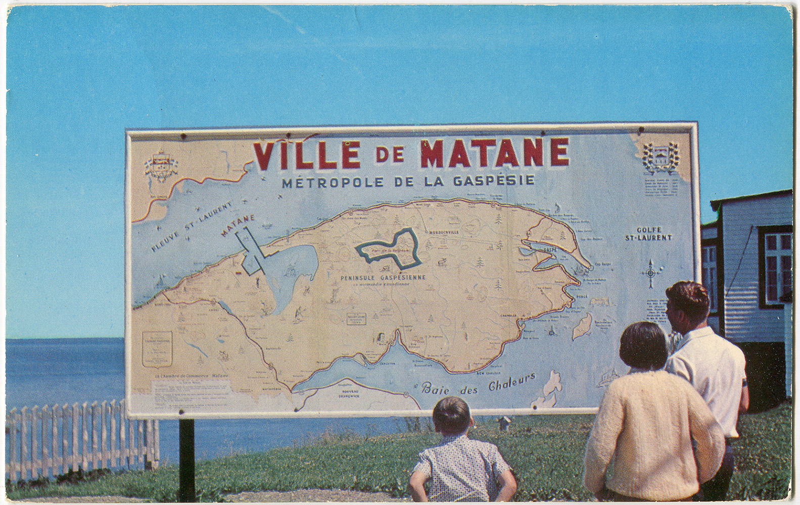 A man, a woman and a child observe a map of the Gaspésie. The map is approximately 4 feet high by 8 feet wide. Located outdoors near the Matane lighthouse, it reads: Ville de Matane 'Métropole de la Gaspésie.