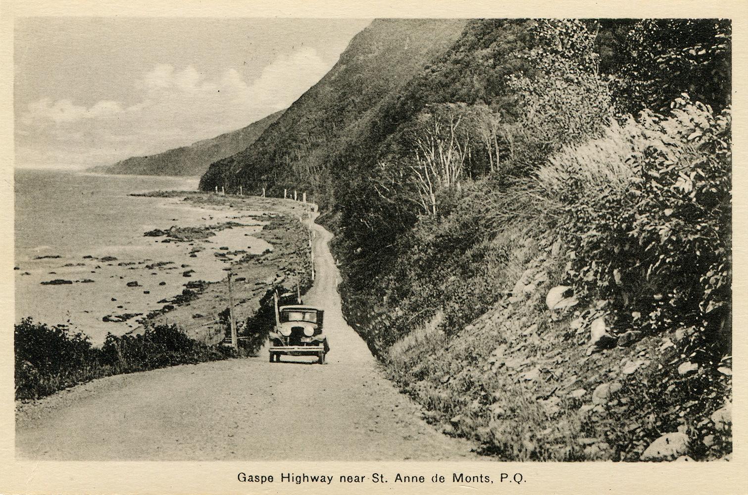 Carte postale présentant une voiture sur le boulevard Perron vers 1930, alors qu'il était en gravier. Le boulevard Perron longe le pied d'une montagne abrupte et la berge du fleuve Saint-Laurent près de Sainte-Anne-des-Monts.
