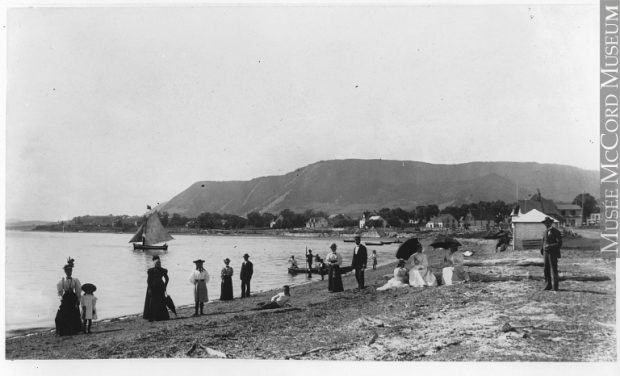 Black and white photograph of a beach. A dozen people pose, men in suits and women in long dresses, some wearing umbrellas. A sailboat and other small boats leave the shore. In the background are some rustic houses at the foot of a mountain.
