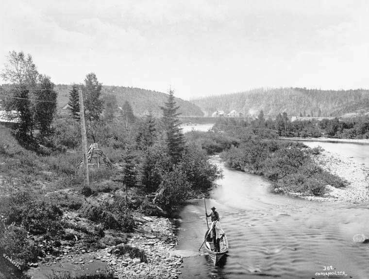 A forest landscape crossed by a river. At the bottom of the photograph, two native men are handling a canoe with poles. On the bank of the river we can see a teepee and, in the distance, some rustic houses at the foot of two hills.