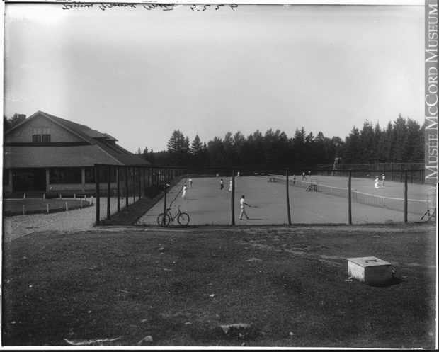 Black and white photograph of a tennis court in Metis Beach. A high fence surrounds the tennis court. Men, wearing white trousers and a white shirt, and women, wearing a long white skirt and a white shirt with long sleeves and hat, are playing tennis. On the left side is the club house of the Cascade Golf and Tennis Club.