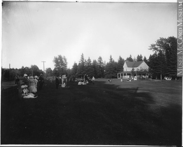 Black and white photograph of the tee off of the golf course of the Cascade Golf Club. Twenty individuals dressed in the fashion of 1914 wait for the tee off on a course. Some women are sitting on the lawn. In the background, a two-storey cottage with simple Victorian architecture.