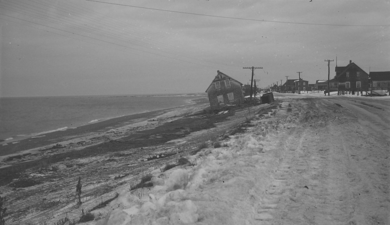 Photograph in black and white of a two-story house at the entrance of a seaside village. The house is on the beach strangely tilted on one side, it appears that it has been moved on the beach side of the road by the waves.