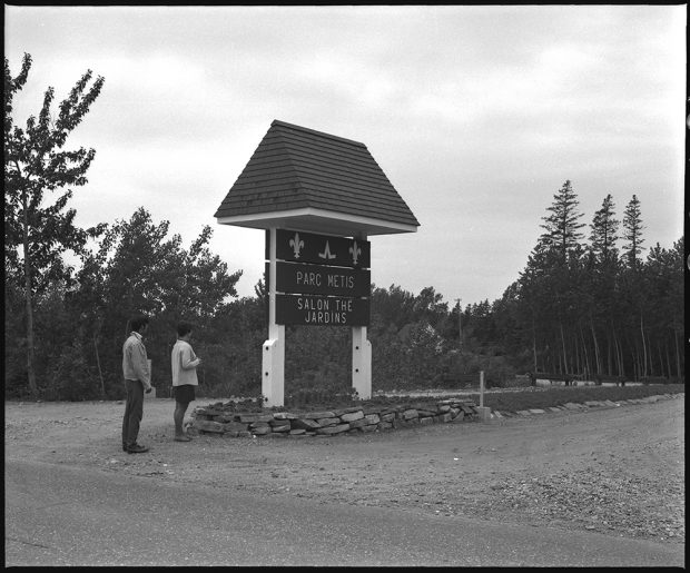 Black and white photograph of the entrance to Parc Metis. A man and a woman observe the sign at the entrance of the site, near Highway 132.