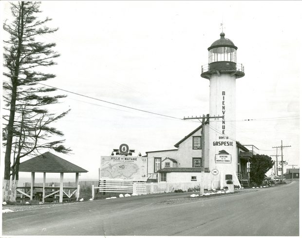 Black and white photograph of the Matane lighthouse, transformed into a tourist information office. Perron Boulevard occupies the foreground of the photograph. The lighthouse and the keeper's house are located on the right side of the image. On the lighthouse is written: Bienvenue dans la Gaspésie. A poster on the lighthouse mentions: Berceau de la Nouvelle-France. A huge map of Gaspésie is displayed near the lighthouse.