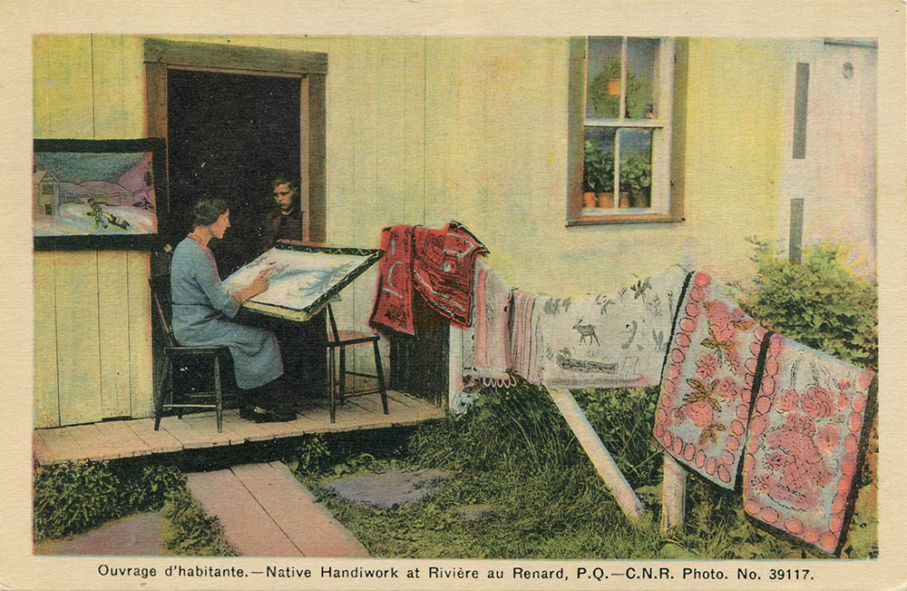 Post card. Hand-painted photography. A woman is sitting on the porch of a house. She paints a winter scene on a canvas whose base is resting on her lap. Near her, six handmade carpets are placed on a fence and a frame, a winter scene is hung on the outside wall of the house. In the opening of the door, a young boy watches his mother stitching a carpet.