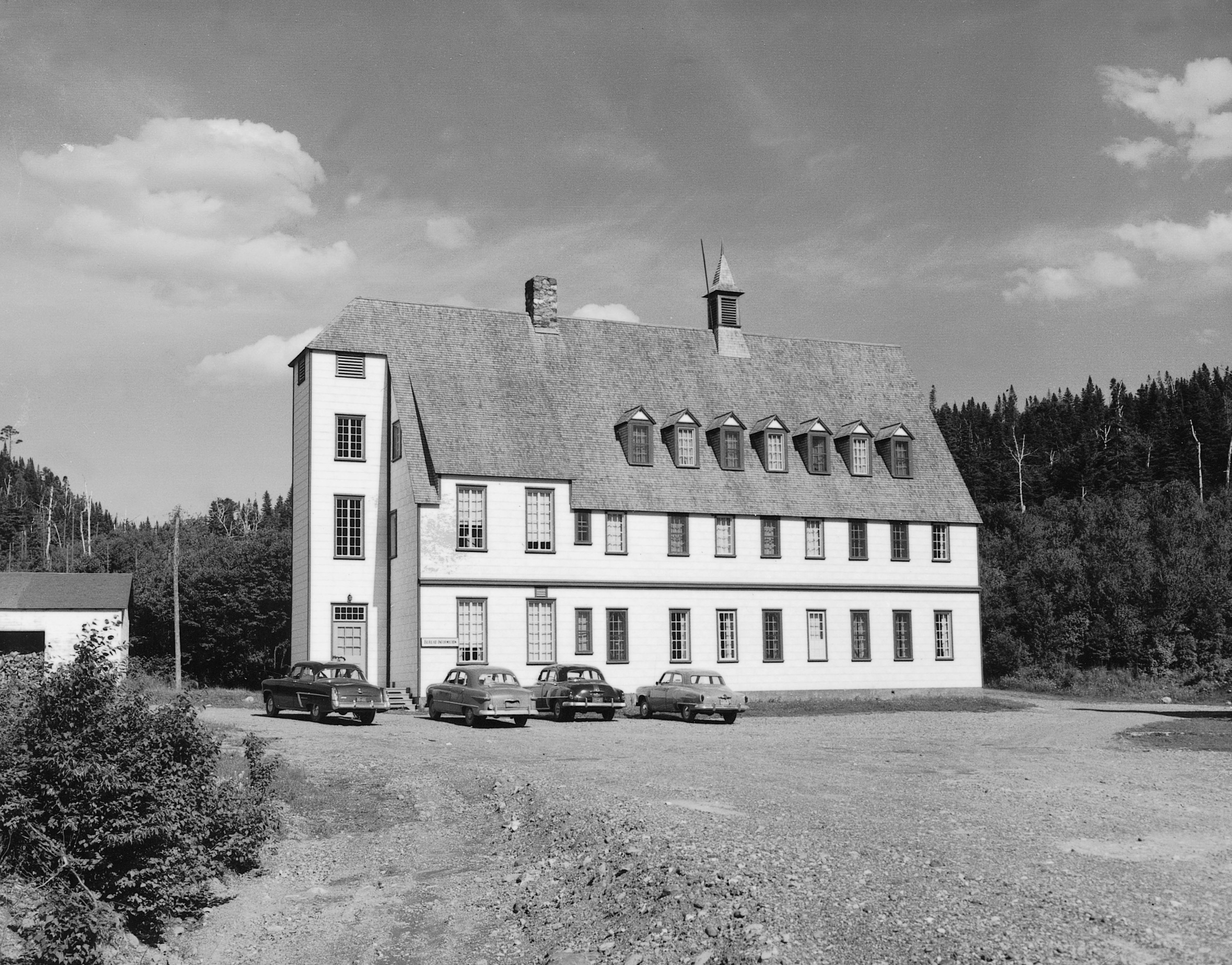 Black and white photograph of the Gîte du Mont-Albert in 1950. The inn is an imposing rectangular building of 3 stories in the heart of a coniferous forest. The pronounced angle of the double slope roof gives it an architectural style that is somewhere between that of a Swiss chalet and a manor house.