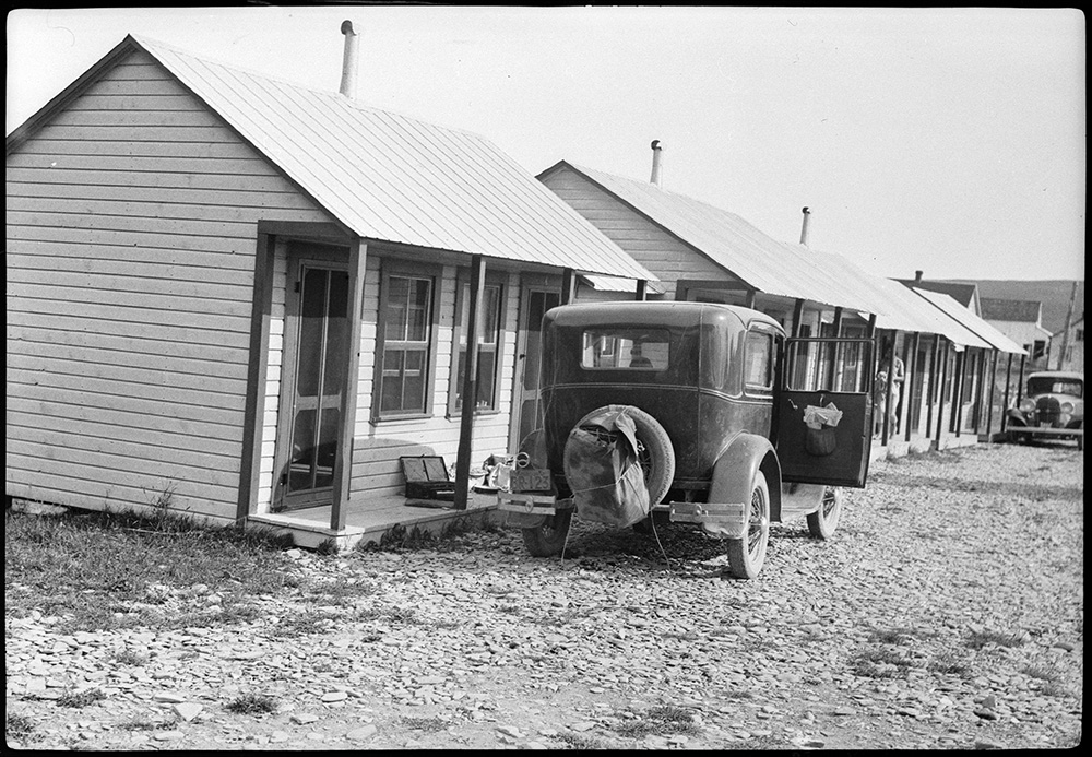 Black and white photograph of a series of tourist cabins in Percé. A 1933 car is parked in front of the first cabin.