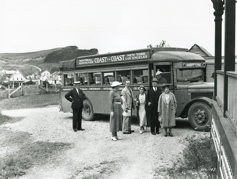 Black and white photograph of a group of people in front of a passenger bus in 1932. Behind the bus, you can see some houses in the village of Percé and the mountains that form the coast. On the bus is written Montreal Vancouver Coast to Coast New York Los Angeles.