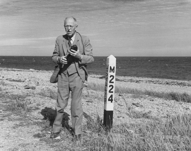 Portrait of George Parmenter. The elderly man, dressed in a jacket and tie, stands with his camera in his hand, near a white post on which it is written M224. In the background the beach of Sainte-Flavie and the sea.