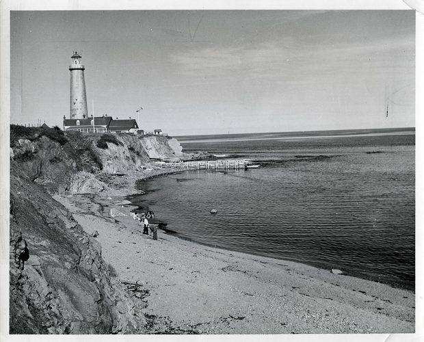 Black and white photograph of the Cap-des-Rosiers lighthouse. In a bay, a family is looking for clams on the beach. In the background, on a rocky cape, you can see the Cap-des-Rosiers lighthouse.