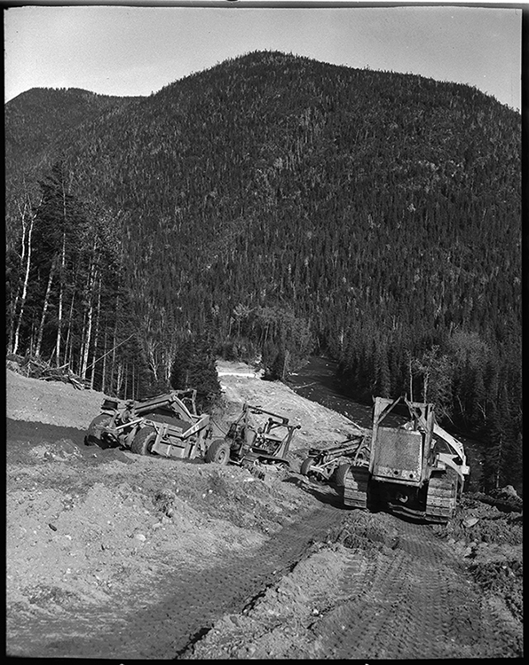 Black and white photograph of the work on the Trans-Gaspésien road. In a forest landscape, on a steep slope, construction workers operate heavy machinery to do the road preparation work.