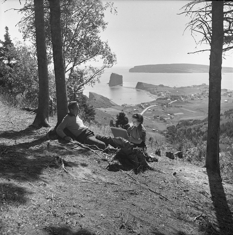 Black and white photograph of the artist Suzanne Guité working on a drawing with her husband as model, artist Alberto Tommi. The couple is sitting at the foot of a tree on top of a mountain. Behind them is a magnificent landscape at the bottom of the mountain the village of Percé as well as Percé Rock.