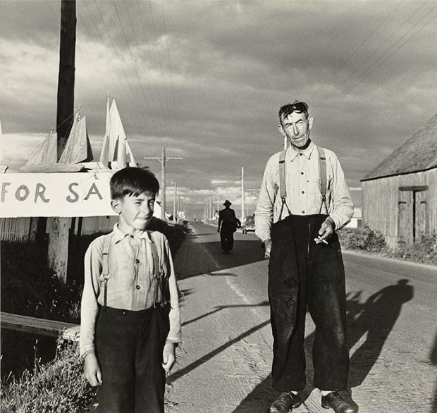 Black and white photograph of a man and a boy on the roadside. The man and the child are dressed in white shirt and black trousers held up by suspenders. Behind the boy wooden boats are placed on the top of a poster on which is written For Sale.