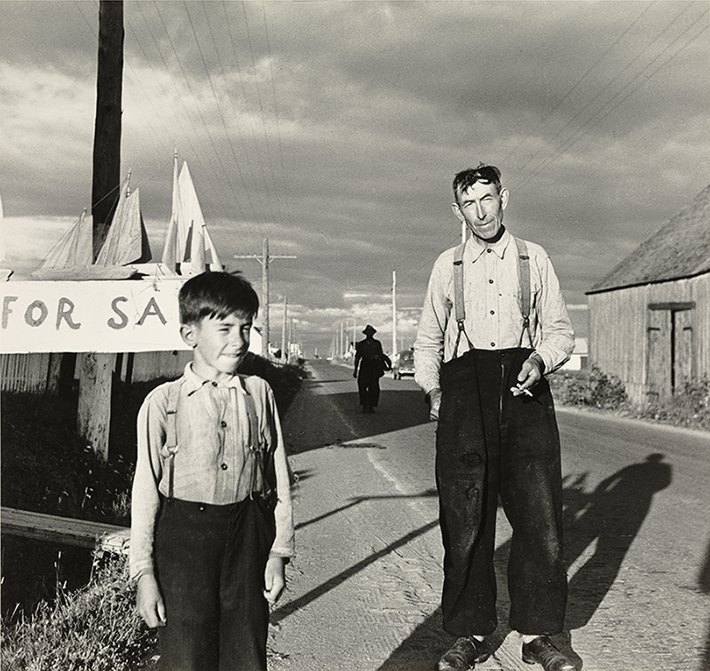 Black and white photograph of a man and a boy on the roadside. The man and the child are dressed in white shirt and black trousers held up by suspenders. Behind the boy wooden boats are placed on the top of a poster on which is written
