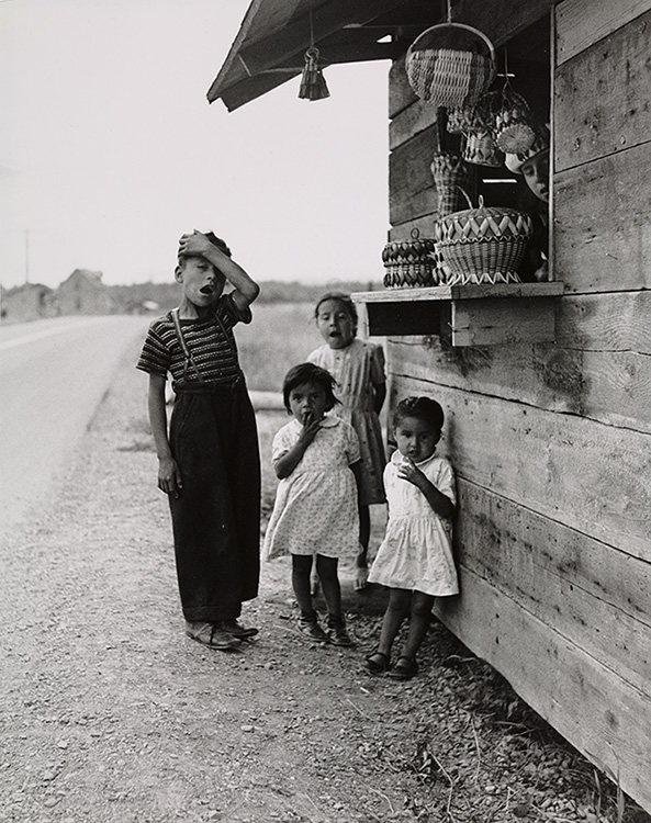 Black and white portrait of four Mi'gmaq children in front of a roadside kiosk selling basketry.