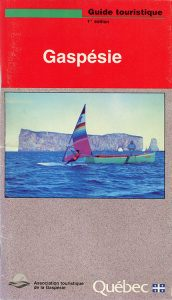 Cover of the first edition of the tourist guide of the Gaspésie region. In the center of the page is a photograph of a fisherman standing in a fishing boat and a man practicing the sport of windsurfing. In the background Percé Rock looms large.
