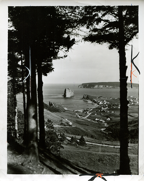 Black and white photography of Rocher Percé. This is one of the most popular viewpoints. The photograph is taken from a high point, at a distance from the Rock, giving a view of the village of Percé, Bonaventure Island and Rocher Percé. The trees on both sides of the photographs create a natural frame of the landscape.