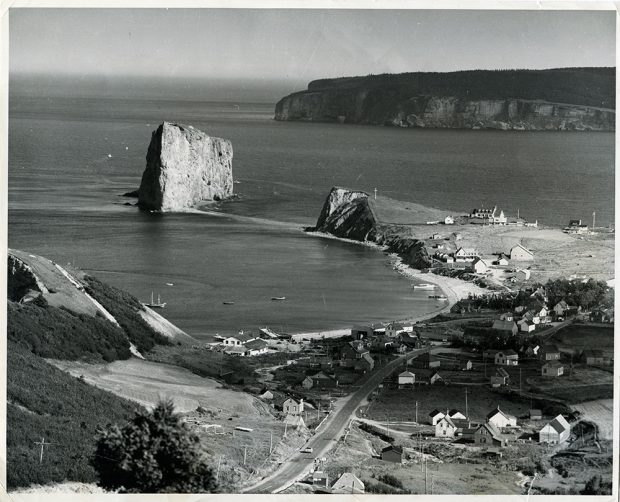 Black and white photograph from a height of land, showing the village of Percé, some fishing boats in the bay, Percé Rock and in the distance, Bonaventure Island.