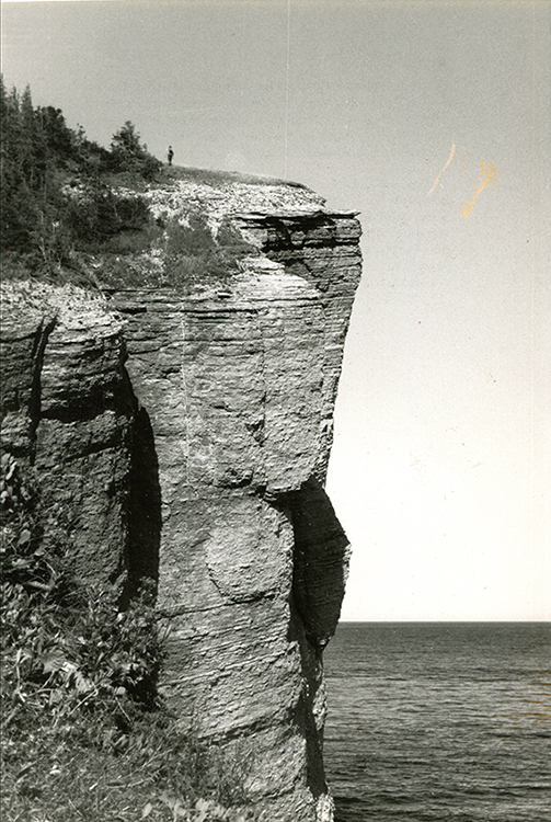 Black and white photograph of a rocky cliff of impressive height. At the top of it is the tiny silhouette of a man. In the background the vast sweep of the Gulf of St. Lawrence.