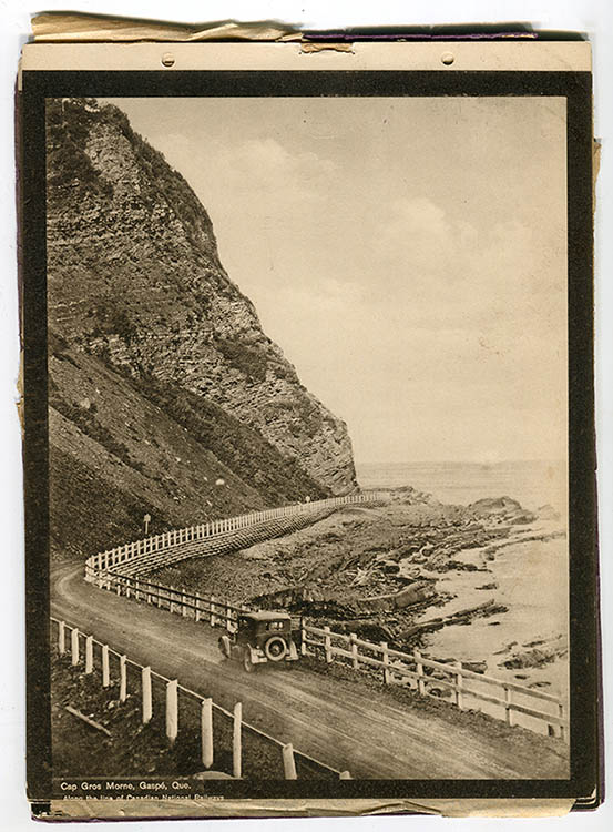 Sepia photograph of a car on the Boulevard Perron consisting of a gravel road winding at the foot of a huge rocky cape in the narrow passage between the cliff and the sea. A simple wooden fence separates the road from the shoreline