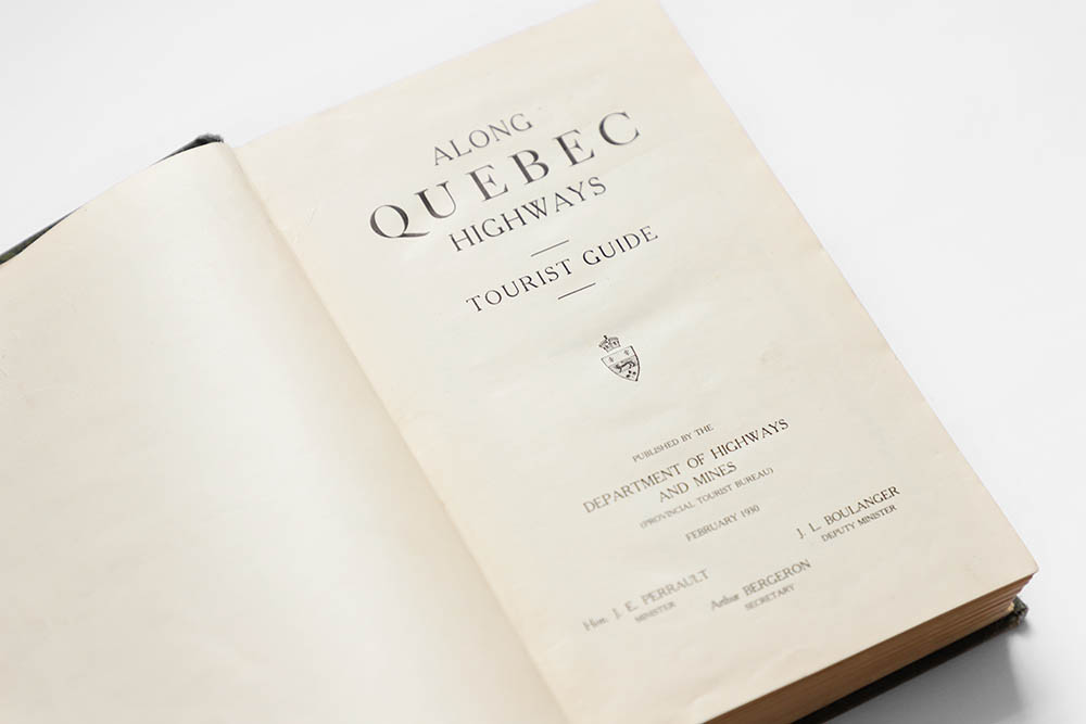 Colour photograph of the title page of the tourist guide Along the Quebec Highways. It is written: Along Quebec Highways Tourist Guide. Published by the Department of Highways and Mines (Provincial Tourism Bureau), February 1930. Names of officials: Minister J. E. Perrault, Deputy Minister J. L. Boulanger and Secretary Arthur Bergeron.