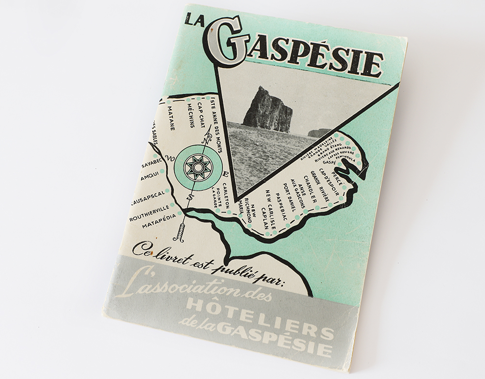 Cover of a tour guide La Gaspésie is drawn in black and white on a pastel green background representing the St. Lawrence River. All villages along the route of Route 6 have been identified. In the top, La Gaspésie is written in big letters. Below, a photograph of Percé Rock is presented in a triangular shape. At the bottom of the page is written This booklet is published by l'Association des Hôteliers de la Gaspésie.