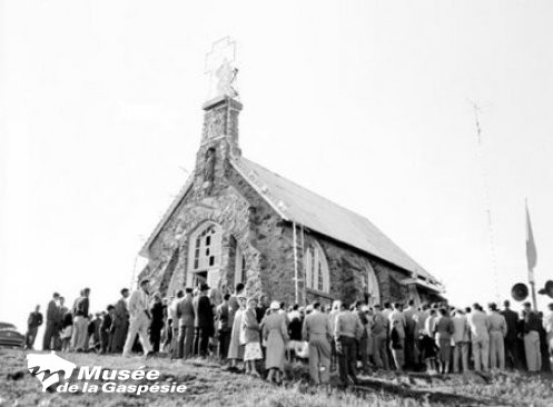 Black and white photograph of the oratory on Mont Saint-Joseph. The oratory is a stone building with a central bell tower on the front with a double slope metal roof. The oratory was built at the top of Mont Saint-Joseph. In front a crowd gathers as part of a celebration.