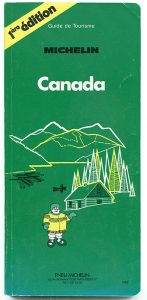 Cover of the first edition of the Michelin Guide. On a green forest green background, the Michelin tire mascot is wearing a coat with bangs. He is wearing snowshoes and a fur hat. Behind him is a log cabin in an evergreen forest near a lake on which there is a canoe and logs. In the background, a chain of mountains.