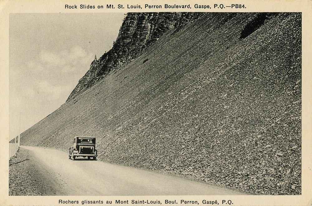 Black and white photograph of a car driving Perron Boulevard. The road follows a steep slope lined with flat rocks, leaving the impression of a recent landslide.